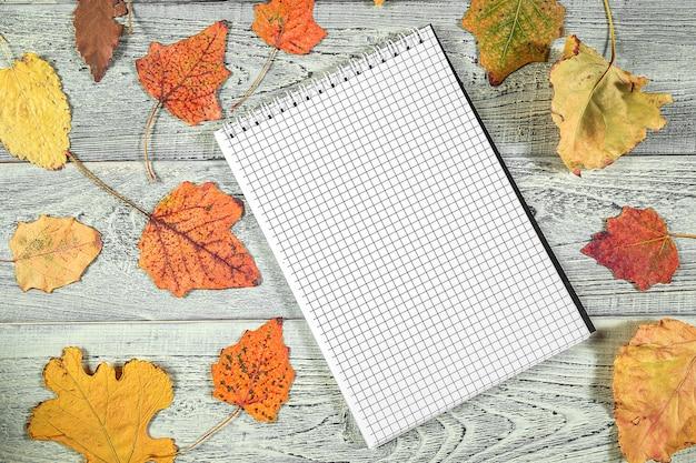Foglie di autunno gialle e un taccuino su un vecchio fondo di legno leggero Foto Premium