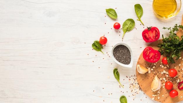 Foglie di basilico; semi di chia; pomodoro e olio divisi a metà disposti sul pavimento di legno bianco Foto Gratuite