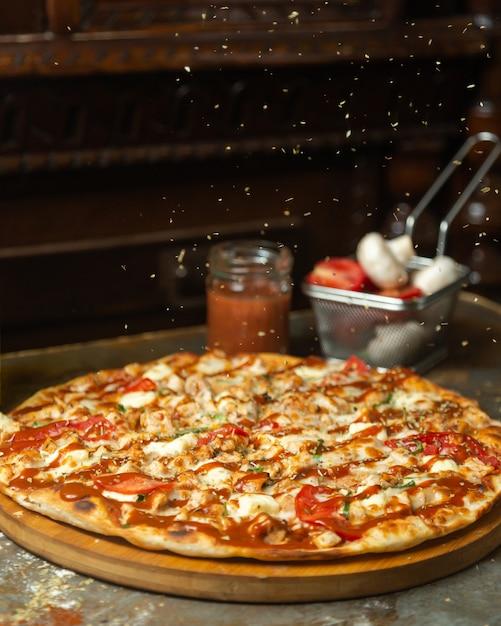 Foglie di menta essiccate sono sparse sulla pizza di pollo Foto Gratuite