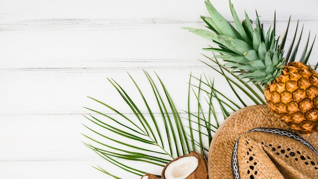 Foglie di piante vicino a frutti tropicali e cappello Foto Gratuite