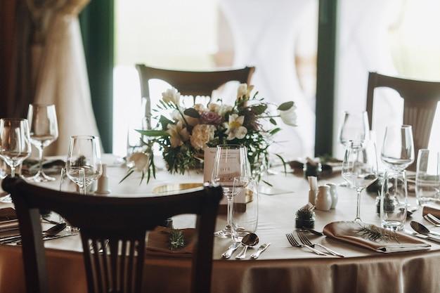 Foglie di pino e bouquet sul tavolo decorato di classe Foto Gratuite