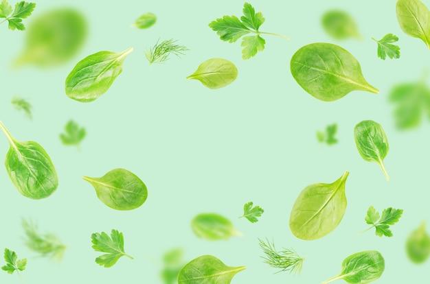 Foglie di spinaci, prezzemolo e aneto in volo su sfondo blu Foto Premium