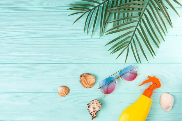 Foglie tropicali con accessori da spiaggia in composizione Foto Gratuite