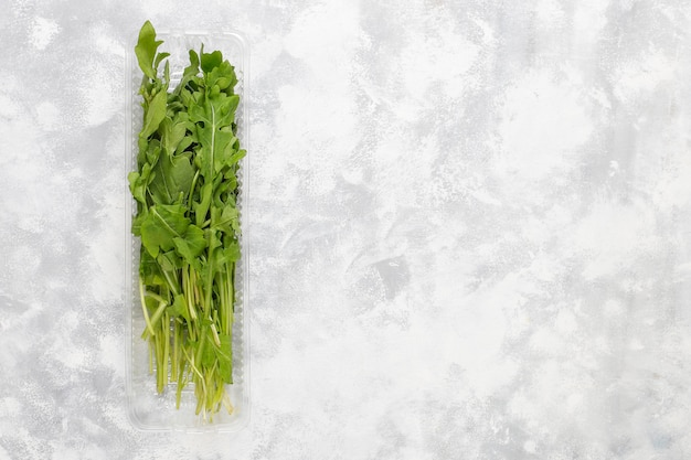 Foglie verdi fresche della rucola o della rucola in scatole di plastica su calcestruzzo grigio Foto Gratuite
