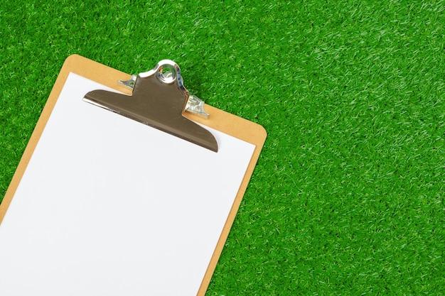 Foglio di carta e attrezzature sportive su erba Foto Premium