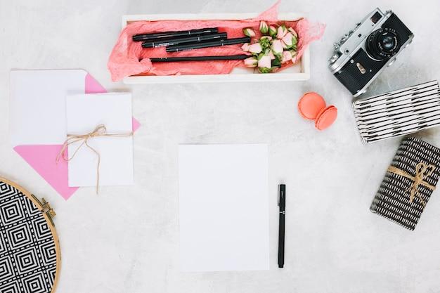 Foglio di carta e penna vicino a regali e fotocamera Foto Gratuite