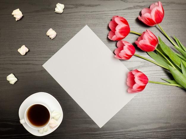 Foglio di carta pulito, tulipani rosa e una tazza di caffè. tavolo nero. vista dall'alto Foto Premium
