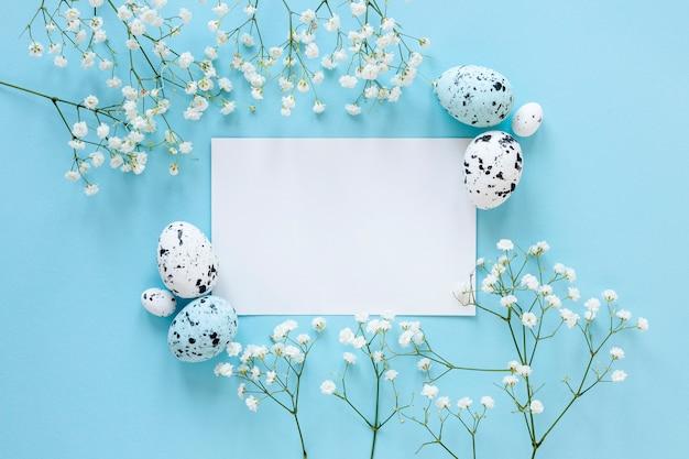 Foglio di carta sul tavolo accanto a uova e fiori dipinti Foto Gratuite