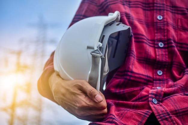Fondo ad alta tensione della centrale elettrica di servizio del responsabile della persona del casco che tiene ingegnere Foto Premium