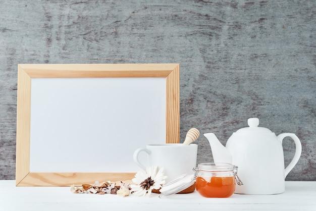 Fondo degli utensili della cucina con libro bianco vuoto, teiera, tazza e un miele in barattolo di vetro Foto Premium