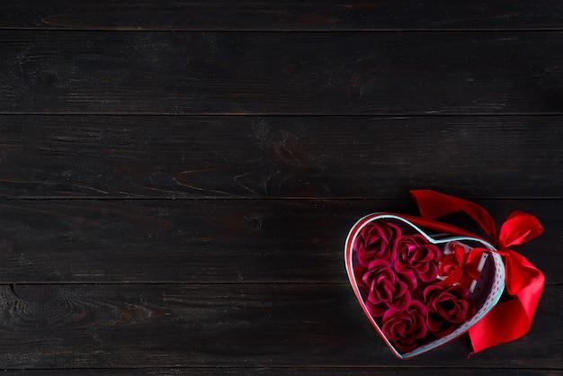 Fondo dei biglietti di s. valentino con mini regalo e rosa in scatola del cuore Foto Premium