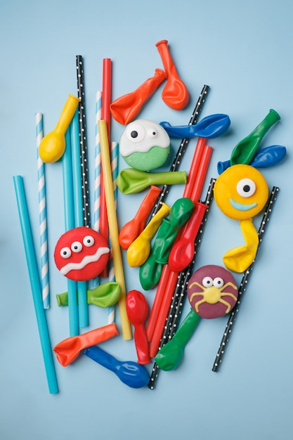 Fondo del partito di halloween di compleanno dei bambini, struttura con i dolci, cannucce del cocktail e palloni sulla superficie del blu Foto Premium