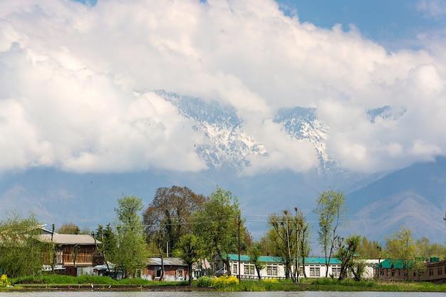 Fondo della montagna del villaggio locale lungo il confine del lago dal a srinagar, kashmir, india Foto Premium
