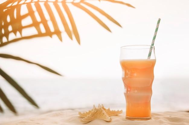 Fondo della spiaggia con cocktail e foglia di palma Foto Gratuite