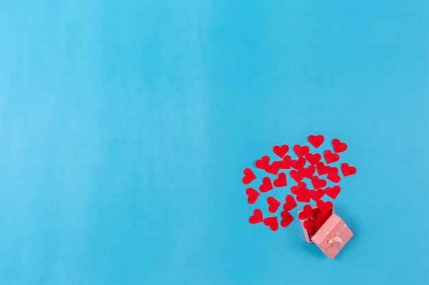 Fondo di giorno di biglietti di s. valentino con cuore rosso e contenitore di regalo su fondo blu. Foto Premium