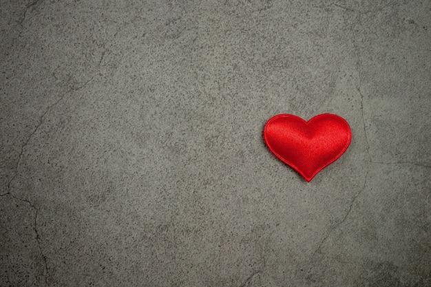 Fondo di giorno di biglietti di s. valentino con i cuori rossi sulla vecchia tavola concreta Foto Premium