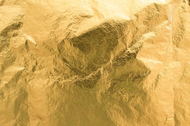 Fondo dorato di struttura della stagnola, elemento brillante della decorazione della carta da imballaggio Foto Gratuite