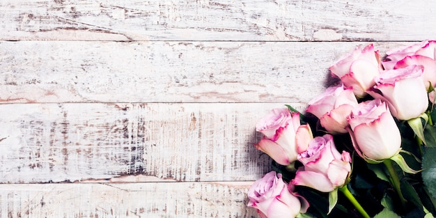 Fondo in legno con bouquet di rose rosa Foto Premium