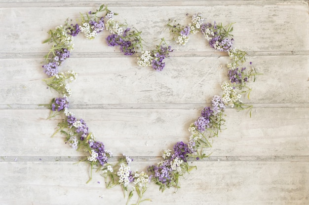 Fondo in legno con cornice floreale a forma di cuore Foto Gratuite
