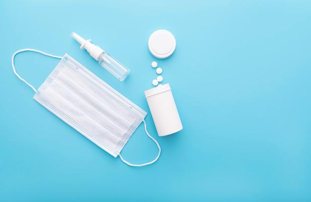 Fondo medico con la bottiglia e le pillole bianche, la maschera medica e lo spray nasale, vista superiore, immagine di concetto Foto Premium