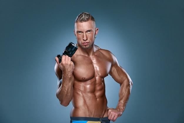 Fondo onblue attraente del costruttore di corpo maschio Foto Gratuite