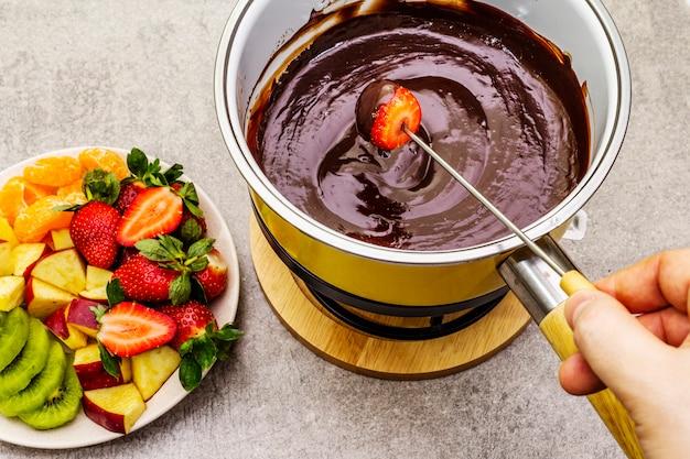 Fonduta di cioccolato assortita con frutta fresca Foto Premium