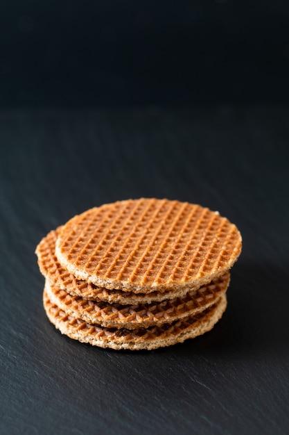 Food concept stroopwafel, sciroppo di caramello croccante waffle olandesi su pietra nera ardesia Foto Premium