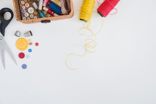 Forbice; pulsanti; ditale; filato rosso e giallo isolato su sfondo bianco Foto Gratuite