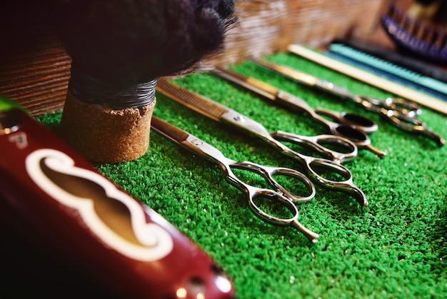 Forbici per il taglio su una stuoia verde nel negozio di barbiere Foto Premium
