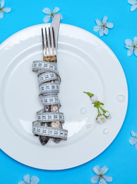 Forchetta con un coltello avvolto in un nastro di misurazione si trovano su un piatto di ceramica rotondo bianco Foto Premium