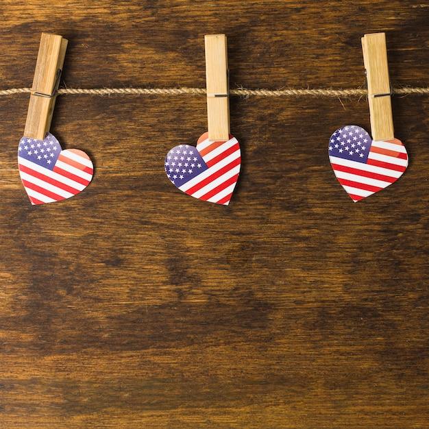 Forma americana del cuore con le mollette da bucato che appendono sulla corda da bucato sopra lo scrittorio di legno Foto Gratuite