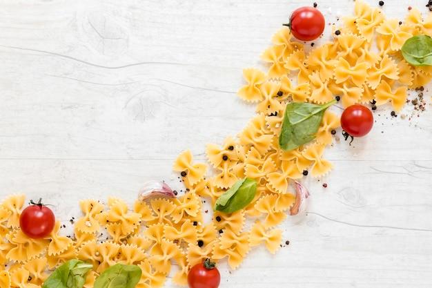 Forma curva realizzata con pasta di farfalle e pomodoro; spicchio d'aglio; foglia di basilico su fondo in legno Foto Gratuite
