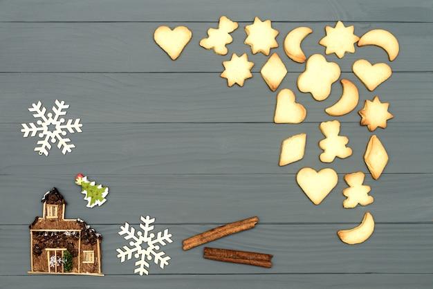Forma dei biscotti di natale della stella, della luna, dell'orso e del cuore con cannella e fiocchi di neve decorativi e casa sul bordo di legno Foto Premium