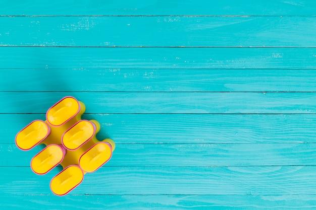 Forma di gelo ghiacciolo giallo su una superficie di legno Foto Gratuite