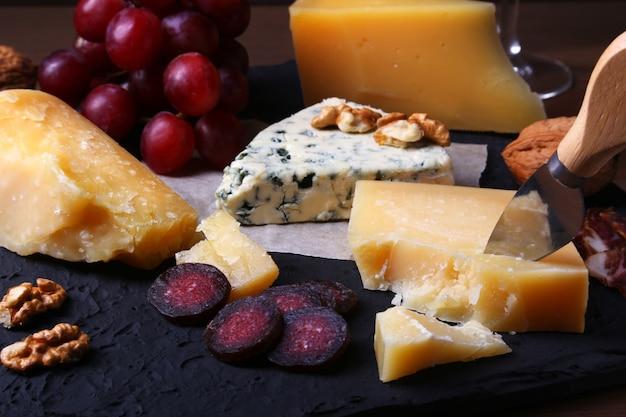 Formaggi assortiti, noci, uva, carne affumicata e bicchiere di vino. Foto Premium