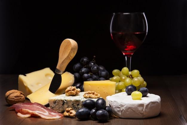 Formaggi assortiti, noci, uva, frutta, carne affumicata e un bicchiere di vino su un tavolo da portata. stile scuro e lunatico. Foto Premium