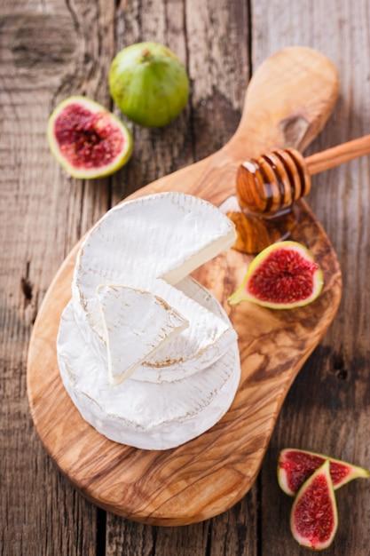 Formaggio brie su una tavola di legno con fichi freschi e miele Foto Premium