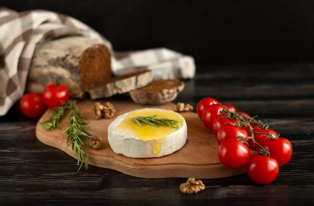 Formaggio camembert con pane di segale, noci, miele, pomodorini e rosmarino su una tavola di legno Foto Premium