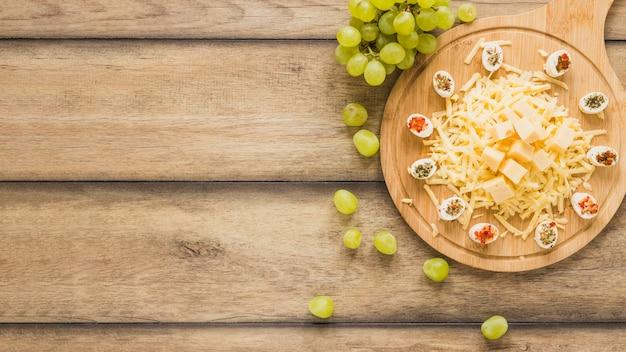 Formaggio con condimenti sul tagliere con uva Foto Gratuite