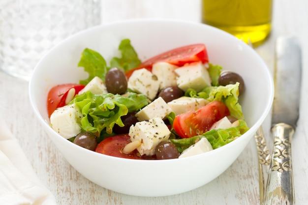 Formaggio di insalata con le verdure in ciotola bianca Foto Premium