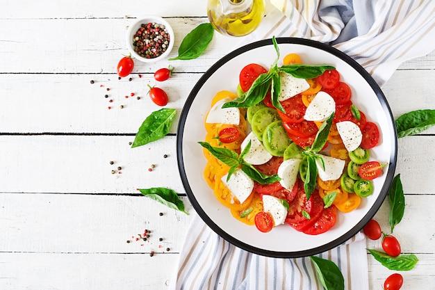Formaggio di mozzarella, pomodori e foglie di basilico erba nel piatto Foto Premium