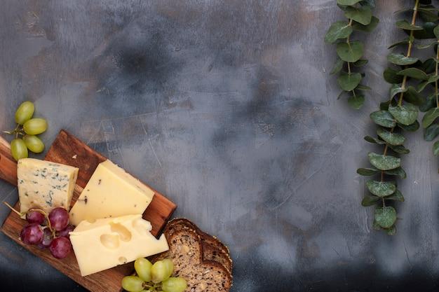 Formaggio e uva su uno sfondo di cemento grigio nero Foto Premium
