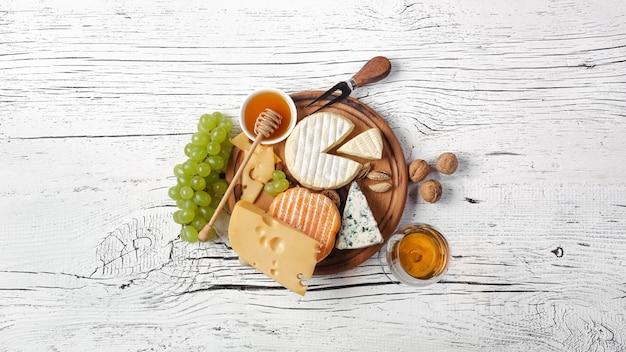 Formaggio, miele, uva, noci e bicchiere di vino sul tagliere e tavolo in legno bianco Foto Premium