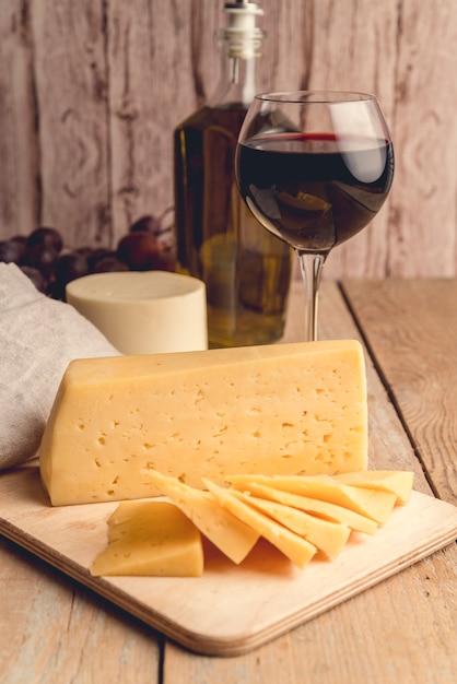 Formaggio saporito del primo piano con un bicchiere di vino Foto Gratuite