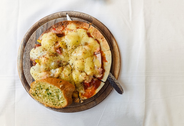 Formaggio sottile di pizza croccante con salmone, prosciutto, pancetta su vassoio di legno Foto Premium