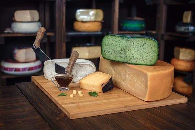 Formaggio teste con fette e coltelli su una tavola di legno con un interno Foto Premium