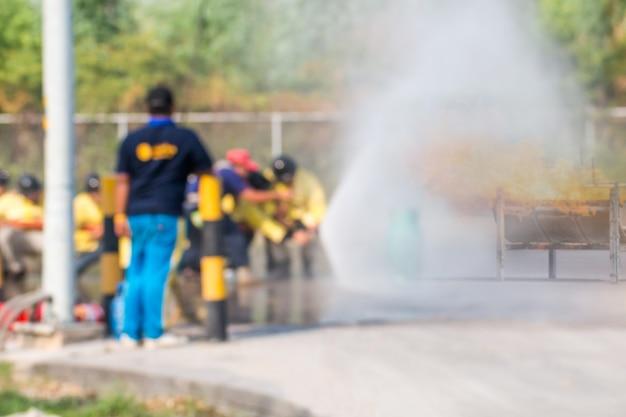 Formazione di vigili del fuoco foto sfocata, i dipendenti formazione annuale antincendio con gas e fiamme Foto Premium