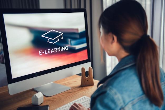 Formazione online, e-learning. la giovane donna è seduta al tavolo, lavorando sul monitor del computer con iscrizione sullo schermo Foto Premium