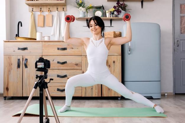 Formazione online. giovane donna allegra che fa le esercitazioni mentre registrando un video di una formazione Foto Premium