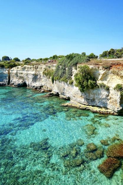 Formazione rocciosa in riva al mare sotto il cielo limpido Foto Gratuite
